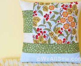 "Is that big, bold scrap of fabric staring at you? This quilt square is designed to let a large print fabric shine. This simple block is quick to make and easily stitched into a pillow. With a bit more fabric you can turn it into a placemat or table runner. The perfect project for turning fabric scraps into something bold and beautiful. Geometric Quilt Block Pillow Supplies Large scraps or fat quarters of 100% cotton quilter's fabrics: One large print One light solid or small print One medium solid or small print One dark solid or small print 1/2 yard of white cotton fabric for the pillow lining 1/2 yard of fabric for the pillow back Coordinating thread 14"" square pillow form Universal or Sharp needle, size 75/11 1/4"" foot (BERNINA Patchwork Foot with Guide #57) Straight stitch foot (BERNINA Straight Stitch Foot #13) Zigzag foot (BERNINA Reverse Pattern Foot #1) or overlock foot (BERNINA Overlock Foot #2) Rotary cutter and self-healing cutting mat Clear acrylic gridded ruler Download and print the Geometric Quilt Block Pillow Cutting and Piecing Diagrams: [download id=""90""] Step 1) Cut the fabric pieces. Accurate cutting helps avoid crooked, puffy, or uneven seams in your quilt block. Use a self-healing mat, a clear acrylic gridded ruler, and a rotary cutter to cut the pieces for your quilt block. Rotary cutters Rotary Cutting Tips Self-healing mats come in different sizes. 24"" x 36"" is a good size to have, but if you don't have a dedicated sewing space or don't plan to use it often, try an 18"" x 24"" mat instead. Acrylic rulers also come in many shapes and sizes. A standard 6"" x 24"" ruler is a good start, and I've also found a 12-1/2"" x 12-1/2"" square ruler to come in very handy. Rotary cutters are measured by the size of the circular blade in millimeters. A 45 mm rotary cutter is perfect for making the kind of straight cuts needed for this project. Use the grid on your cutting mat to help square up fabric pieces when needed, but when measuring to cut the pieces be sure to use the gridlines on the acrylic ruler. Hold the ruler firmly on top of the fabric, and use a steady, firm, pressing motion when cutting with the rotary cutter. Cut one of each pattern piece from the corresponding fabrics (also see downloaded Cutting Diagram): Piece #1 - Light solid or small print, 4"" x 3"" Piece #2 - Dark solid or small print, 4"" x 5"" Piece #3 - Light solid or small print, 4"" x 2-1/2"" Piece #4 - Large print, 9-1/2"" x 9-1/2"" Piece #5 - Light solid or small print, 2-1/2"" x 9-1/2"" Piece #6 - Dark solid or small print, 14-1/2"" x 2-1/2"" Piece #7 - Medium solid or small print, 14-1/2"" x 3-1/2"" Step 2) Piece the block. Set your sewing machine for a straight stitch about 2.5 mm long. Attach a quarter-inch foot, such as BERNINA Patchwork Foot with Guide #57, to your sewing machine. The blocks will be sewn together using a 1/4""-wide seam allowance. Stitching an accurate 1/4""-wide seam will help your block come together with nice, straight seams and avoid pieces not fitting together as you sew on. Geometric Quilt Block Pillow Patchwork Piecing Tips Us a quarter-inch foot to help you keep the correct seam allowance width. The BERNINA Patchwork Foot #37 is designed specifically so that following the edge of the foot will create a 1/4""-wide seam allowance. BERNINA Patchwork Foot with Guide #57 is similar to foot #37, but adds a metal guide at the side of the foot to help you like up your fabric piece exactly at the edge of the foot. Attach a seam guide to the bed of your sewing machine along the 1/4"" seam allowance mark on your stitch plate, then place the edges of your fabric pieces against the guide as you sew. Alternatively, place a piece of blue low-tack painter's tape along the 1/4"" seam allowance mark on your stitch plate as a guide for your fabric. Piecing Diagram Geometric Quilt Block Pillow Start by stitching Piece #1 to Piece #2 along one 4"" edge. Press the seam allowances to one side. Next, sew Piece #3 to Piece #2 along one 4"" edge as shown in the diagram; press after stitching. Geometric Quilt Block Pillow Continue adding pieces to the block as shown in the diagram, pressing each seam as you go. Tip: When pressing seams, be sure to press DOWN with the iron as opposed to ""ironing,"" or pushing the iron back and forth over the seam. Ironing (back and forth motion) can cause straight seams to go crooked. Pressing straight up and down with the iron will help your seams stay nice and straight. Press all seams again from the back of the block when finished. Geometric Quilt Block Pillow The finished block should measure 14-1/2"" x 14-1/2"". Geometric Quilt Block Pillow Step 3) Construct the pillow cover. Cut one 14-1/2"" x 14-1/2"" square of fabric for the pillow lining. Cut two 11"" x 14-1/2"" rectangles of fabric for the pillow back. Create a 2"" hem along one edge of each 11"" x 14-1/2"" pillow pocket piece: Turn under 1"" along one long edge; press. Turn under an additional 1""; press. Geometric Quilt Block Pillow Topstitch close to the inner edge of the folded hem with a straight stitch, using either a multi-purpose foot or a straight stitch foot. Geometric Quilt Block Pillow Layer and pin the pieces of the pillow together: Begin with the 14-1/2"" square of white cotton for the lining. Add the finished patchwork block, right side up, matching all edges. Add one pocket pillow back, right side down, matching the raw edges. The finished hem will be about 5"" from the other end of the pillow. Add the other pocket pillow back, right side down, on the opposite edge. The hemmed edges will overlap. Geometric Quilt Block Pillow Pin around all four edges of the pillow. Set your sewing machine for a straight stitch of 2.5 mm long. Stitch around all four sides of the pillow using a 1/2""-wide seam allowance. Trim all seam allowances to 1/4"". Attach an overlock or zigzag stitch foot to your sewing machine. Set your machine for a zigzag or overlock stitch and sew over the raw edges to keep them from unraveling. Geometric Quilt Block Pillow Turn the pillow cover right side out, gently pushing each corner from the inside to turn it. Insert the 14""-square pillow form through the opening in the back of the pillow cover. If needed, use a little fiberfill to help fill out the pillow corners. Geometric Quilt Block Pillow Geometric Quilt Block Pillow"