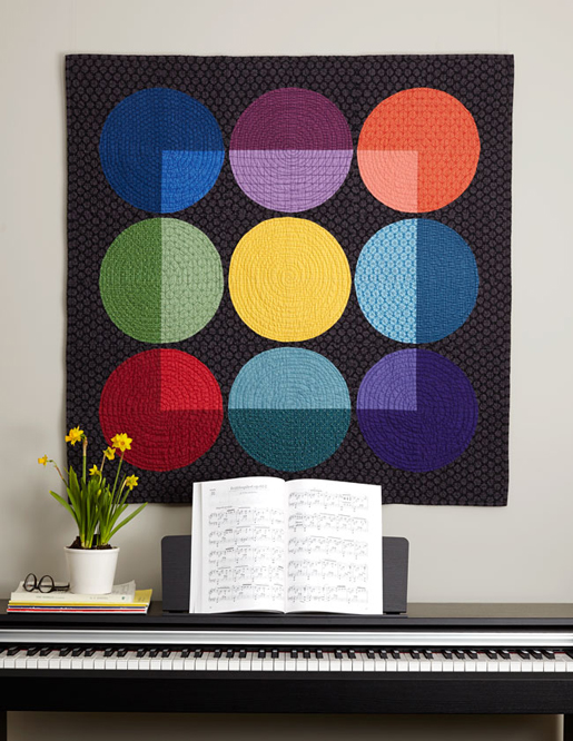 black quilt with circles in nine colors