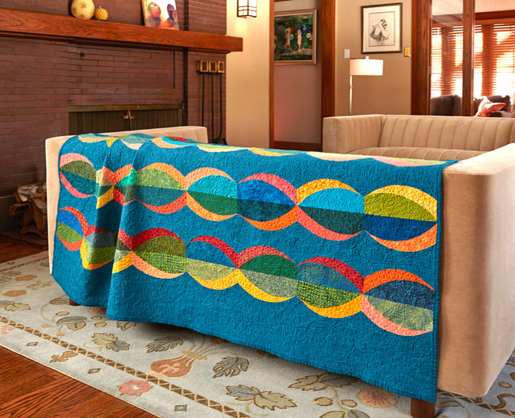blue quilt with orange and yellow waves