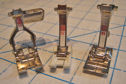 three sewing machine presser feet