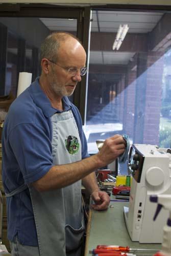 sewing-machine-technician-wiping-the-machine