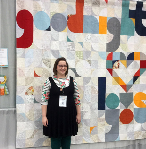 Laura Hartrich with her quilt, Quilt for Our Bed