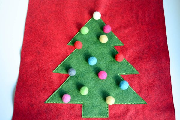 Christmas Tree Pillow Tutorial - Arrange the pom poms on the pillow front to your liking