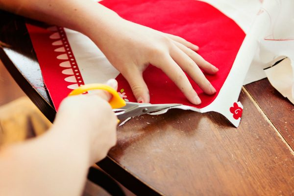 Little girl cutting out pattern on cloth