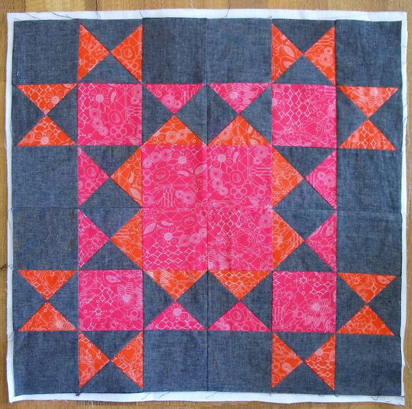 Seam the four blocks together with the pink corner square facing the center of the large 24 ½″ square