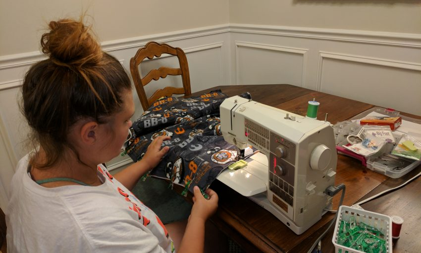 Granddaughter learns to sew